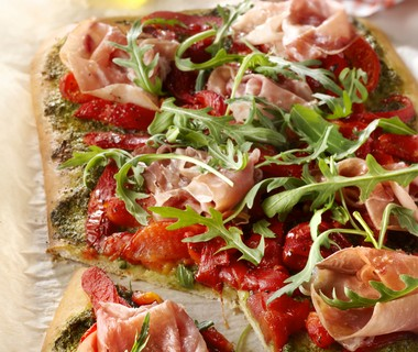 Pizza met rauwe ham, paprika en rucola