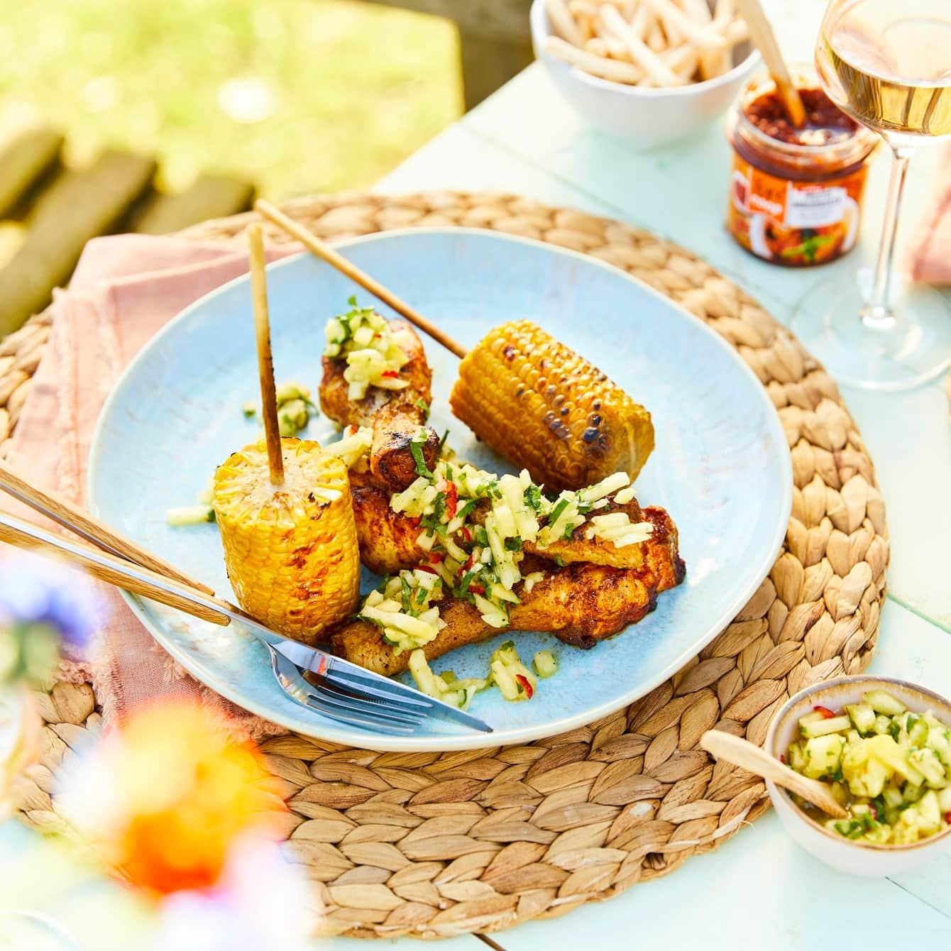 Drumsticks van de barbecue met een tropische ananassalsa en gegrilde maiskolven