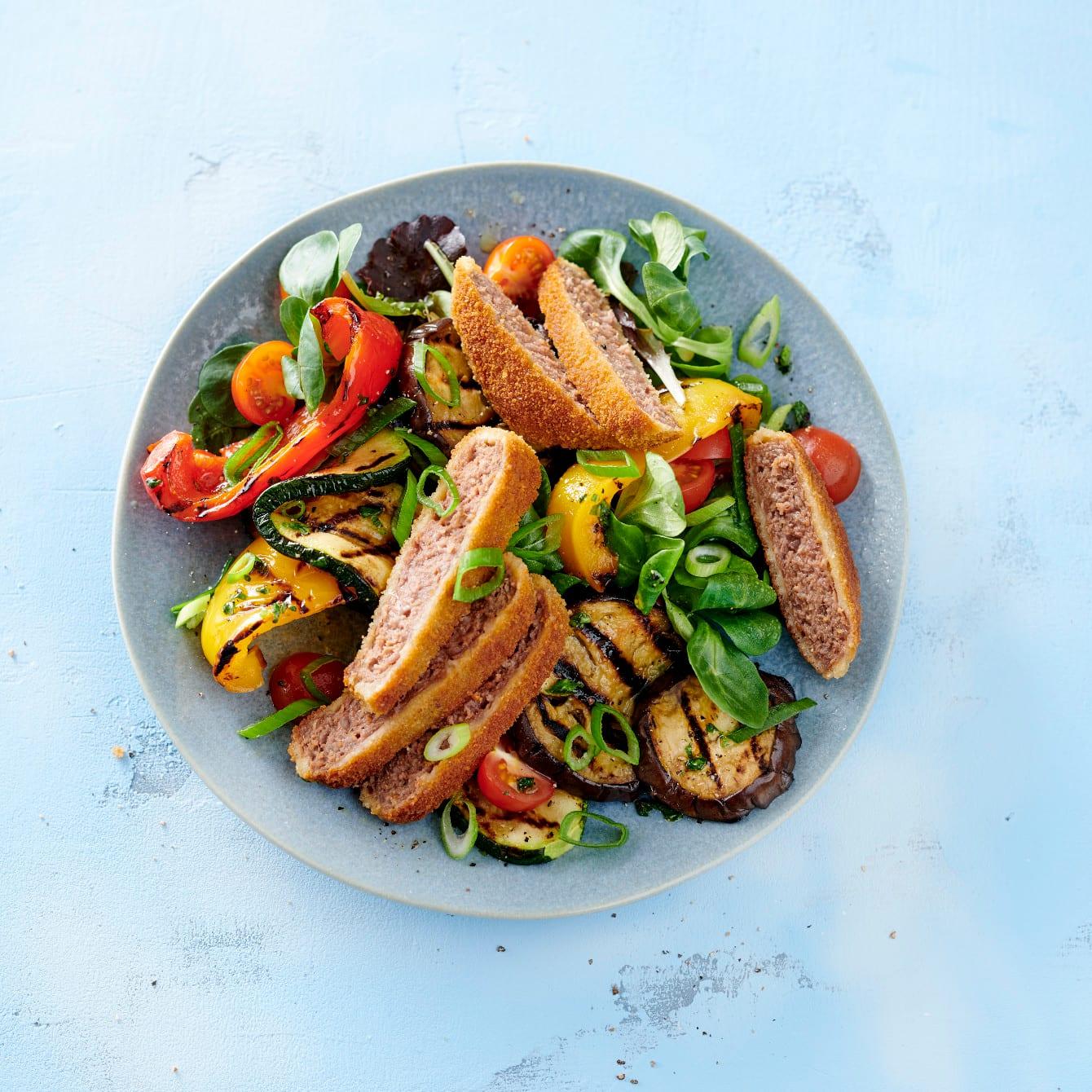 Salade met gepaneerde hamburgers en gegrilde groenten