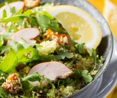 Lauwwarme couscoussalade met rozijnen en gerookte kip