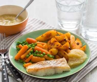 Kabeljauwfilet met doperwten, wortelen en gekruide aardappelpartjes